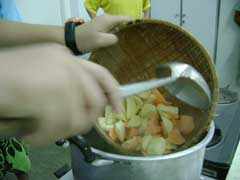 putting potatoes into boiling syrup