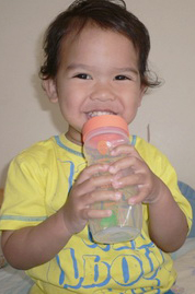 A happy toddler with a Tiwi baby tupperware bottle
